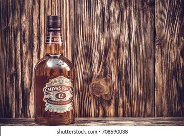Ternopil, Ukraine - August 26, 2017: Bottle of Blended scotch whisky Chivas Regal. 12 years old scotch whiskey. Made in Scotland. Bottle of whisky on wooden background. Toned.