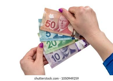 Ternopil, Ukraine - Febryary 13, 2018:Canadian dollar on female hand isolated on white