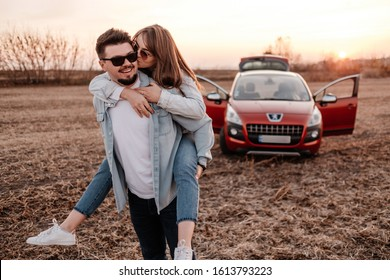 TERNOPIL, UKRAINE - OCTOBER 25, 2019: Young Happy Couple Dressed Alike in White Shirt and Jeans Enjoying Road Trip at Their New Brand Suv Car, Crossover Peugeot 3008