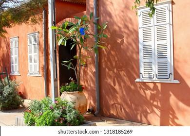 Terra cotta walls, white shutter windows, garden plants and pots, Neve Tzedek quarter, Tel Aviv