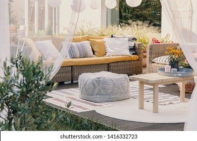 Terrace design idea with rattan garden furniture set and cozy pillows and rug, real photo