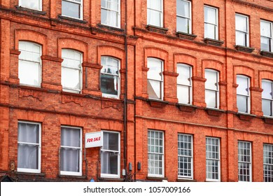 Terrace of grand red brick houses with FOR SLAE sign around Camden Town in London