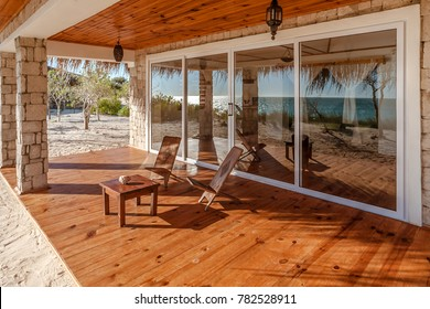 Terrace of a luxurious bungalow with reflection of the sea in the patio door