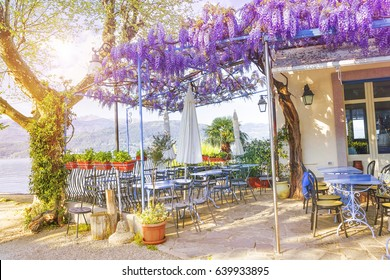 Terrace of outdoor small retro cafe decorated with flowers of wisteria on the Italian coast in a sunny spring evening. Lake Lago Maggiore in Stresa, Italy.