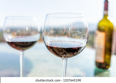 Terrace patio in Italy with bottle and two glasses macro of red wine on glass table with bokeh background of mountains