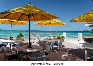 Terrace of a restaurant with yello sun shades on a beautiful caribbean beach