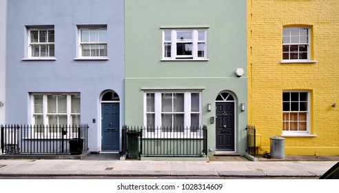 A terrace of small old painted townhouses in the Royal Borough of Kensington and Chelsea, London, UK.