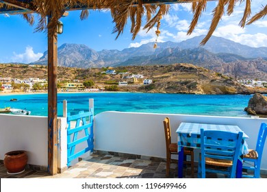 Terrace with table in traditional Greek tavern in Lefkos port on Karpathos island, Greece