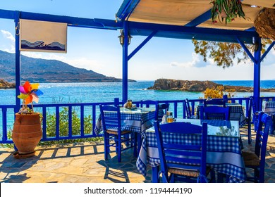 Terrace with tables in traditional Greek tavern with sea view in Lefkos village on Karpathos island, Greece