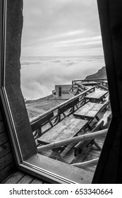 Terrace with tables, wooden benches, cabin and clouds cover at the horizon framed through a window, Black and white.