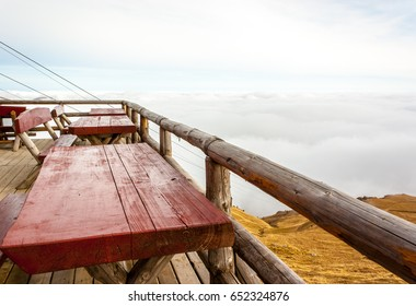 Terrace with tables and wooden benches on mountain summit. Clouds cover and cable seen in the background.