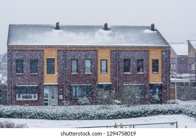 terraced houses on a cold and snowy winter day, modern dutch architecture, snowfall in a small dutch village
