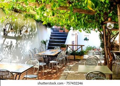 Terraced patio of the italian restaurant  under lemon tree in Amalfi town, Italy