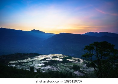 Terraced rice field in water season by sunset period, the time before starting grow rice in Y Ty, Lao Cai province, Vietnam