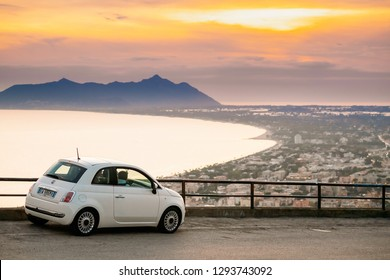 Terracina, Italy - October 15, 2018: White Color Fiat 500 Facelift 2016 Car Parked On Background Circeo Promontory And Tyrrhenian Sea In Sunset Or Sunrise Time