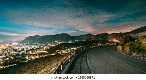 Terracina, Italy. Top View Skyline Cityscape City In Evening Night Illuminations. Night Open Road And Beautiful Cityscape. Panorama, Panoramic View.
