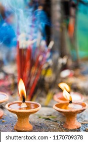Terra-cota oil lamps as religious offerings at temple in Nepal. Incence sticks over blurred background.