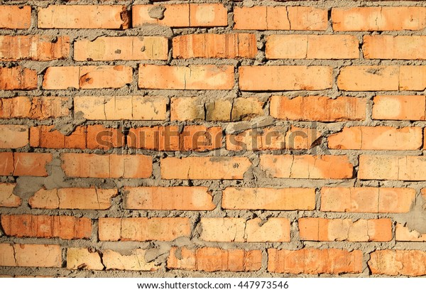 terracotta brick wall. / New brick wall, terracotta color with the remains of cement and coarse stitching, illuminated by bright sunshine.