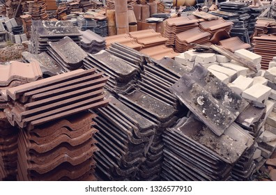Terracotta and composite reclaimed roof tiles at a salvage yard in the UK.