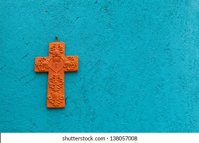 Terracotta cross on a turquoise textured wall in Mexico, abstract vibrant background. Old adobe wall. Mexico travel background.