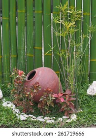 Terracotta pot with garden plants and bamboo wall