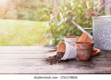 Terracotta pots & soil on a gardening bench outdoors on a sunny summer day. Extreme shallow depth of field with selective focus on center of table and blurred plants and garden shed in the background.