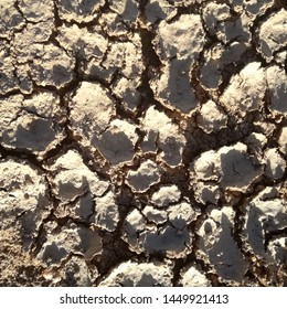 Terrain with cracks. Absence of rain. Severe drought. Brown dry land. Rural area of the center of the Iberian Peninsula, Spanish countryside.
