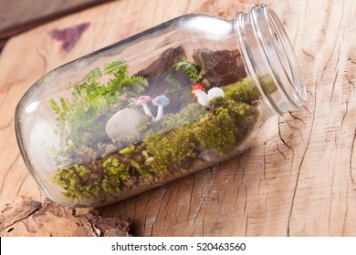A terrarium garden scene in a clear bottle with moss, pebble, chicken and mushroom toy put on wooden table