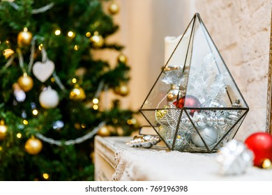 Terrarium glass with christmas decorations on the fireplace, lights bokeh