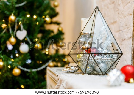 terrarium glass with christmas decorations on the fireplace lights bokeh