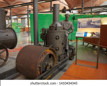 Terrassa, Spain - July, 25th, 2018: Photo of an old, rusty steam steamroller with a mannequin as shown in the mNACTEC museum.