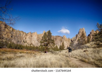TERREBONNE, OREGON - NOV 6, 2017 - Hiker with bninoculars watching climbers on  the jagged peaks of Smith Rock State Park, Oregon