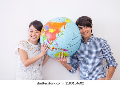 A terrestrial globe and man and woman