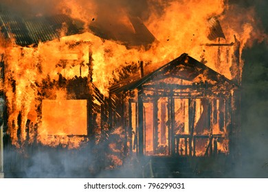 Terrible close up of burning house. Fire destroys a whole wooden building.