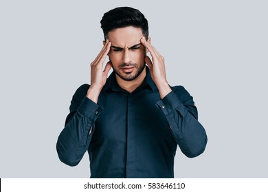 Terrible headache. Frustrated young man touching his head with hands and making face while standing against grey background