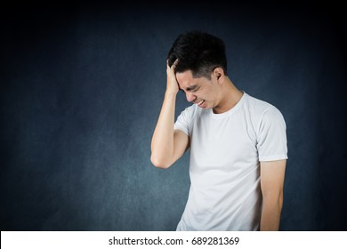 Terrible headache portrait handsome young asian man wearing a white t-shirt  isolated on black background. Businessman concept. Asia people.