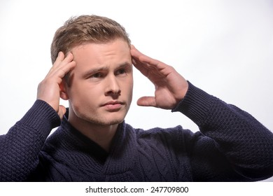 Terrible headache. Young handsome man in cardigan touching his head and looking away while standing against white background