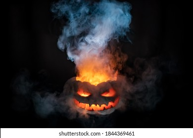 A terrible pumpkin with burning eyes, a cloud of smoke enveloped it. Halloween is coming soon