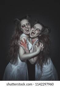 Terrible screaming vampires with horns on dark background