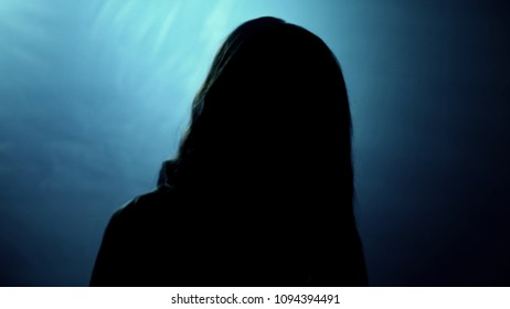 Terrible silhouette of female looking into camera, victim of crazy murderer