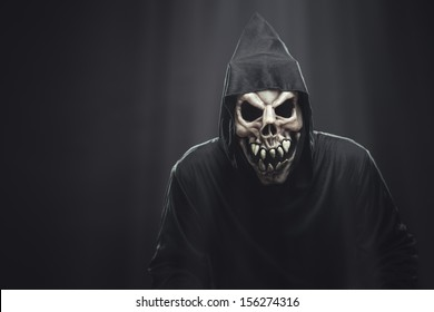 terrible skeleton in a black robe standing in the dark under the rays of the moon