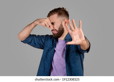 Terrible smell concept. Millennial hipster guy closing his nose and gesturing STOP, feeling disgusted on grey studio background. Young man repulsed by unpleasant odor or stinky perfume