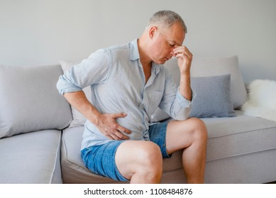 Terrible stomachache. Frustrated handsome young man hugging his belly and keeping eyes closed. Businessman stomachache. Mature man sitting with stomach pain