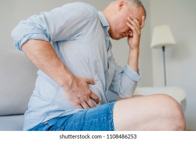 Terrible stomachache. Frustrated handsome young man hugging his belly and keeping eyes closed. Disturbed male having pain in stomach