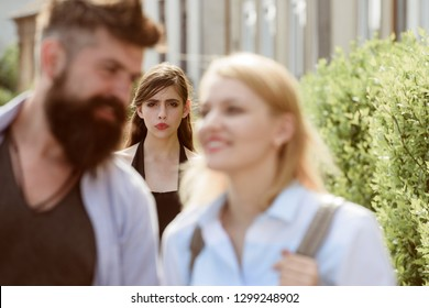 Terribly jealous of them. Romantic couple of man and woman dating. Bearded man cheating his girlfriend with another woman. Jealous woman look at couple in love on street. Unhappy girl feeling jealous.
