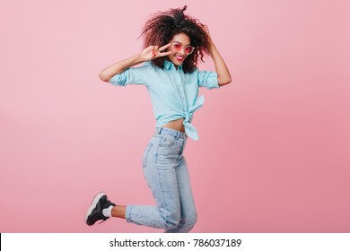 Terrific dark-haired lady in trendy jeans dancing with hands up. Amazing black young woman with brown curls enjoying photoshoot on pink background.