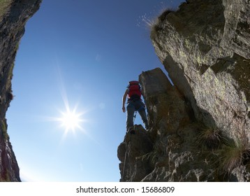 Terrific view of a climbing route: climber standing on the rocky ridge, back-light, fish-eye lens.