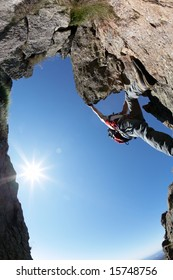 Terrific view of a climbing route: young man climbing a rocky ridge, back-light, fish-eye lens, vertical frame.