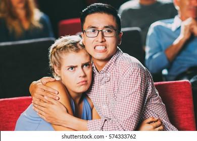 Terrified couple watching horror movie in cinema
