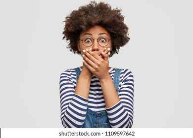 Terrified dark skinned cute young female with Afro hairstyle, covers mouth with great fear, tries not to cry, has scared shocked expression, wears striped sweater, isolated over white background.